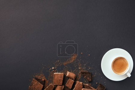 top view of arranged cup of coffee, truffles and chocolate bars with cocoa powder on grey tabletop