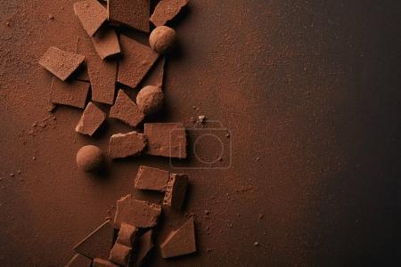 Photo for Flat lay with arranged truffles and chocolate bars with cocoa powder on tabletop - Royalty Free Image