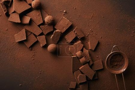 top view of arrangement of various types of chocolate, truffles and sieve with cocoa powder