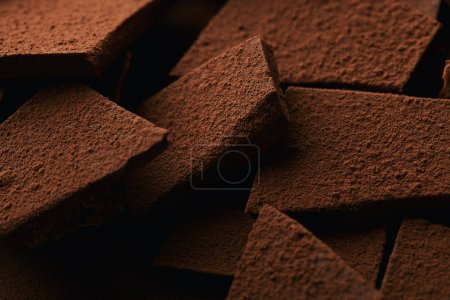 Photo for Close up view of heap of chocolate bars in cocoa powder - Royalty Free Image