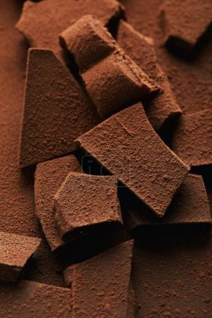 Nahaufnahme eines Haufens von Schokoriegeln in Kakaopulver
