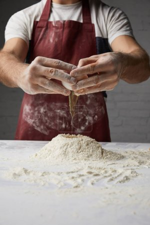 Photo for Cropped image of chef preparing dough and adding egg - Royalty Free Image