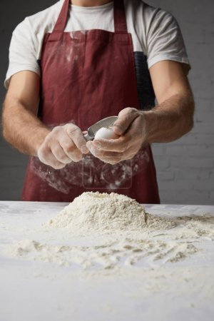 cropped image of chef preparing dough and breaking egg