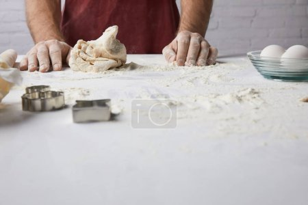 cropped image of chef standing at table with dough