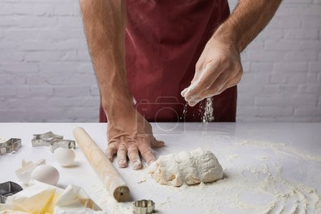 Photo for Cropped image of chef adding flour to dough - Royalty Free Image