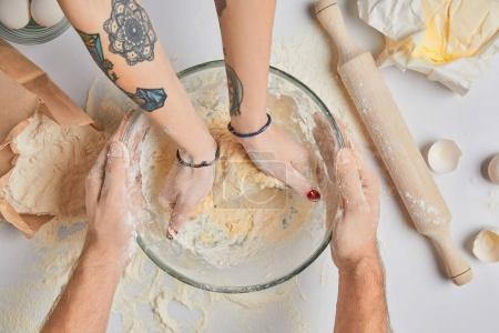 cropped image of chefs kneading dough
