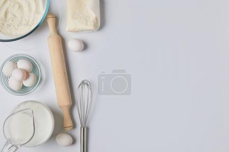 Photo for Top view of eggs, milk and rolling pin on white tabletop - Royalty Free Image