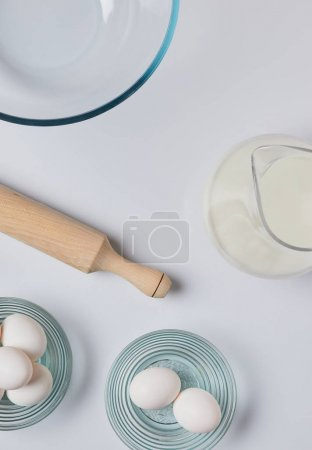 top view of eggs, milk and rolling pin on table