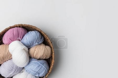 Foto de Vista superior de bolas de hilo de colores en canasta de mimbre sobre fondo blanco - Imagen libre de derechos