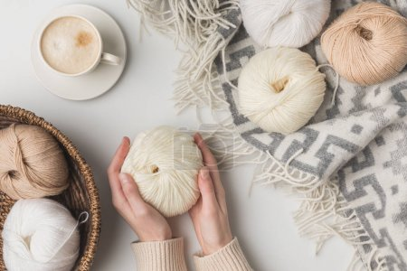 Photo for Cropped view of woman holding cup of coffee and yarn balls on blaket and in basket on white background - Royalty Free Image