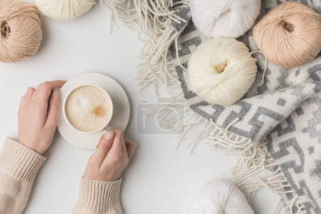 cropped view of woman holding cup of coffee and yarn balls on blaket on white background