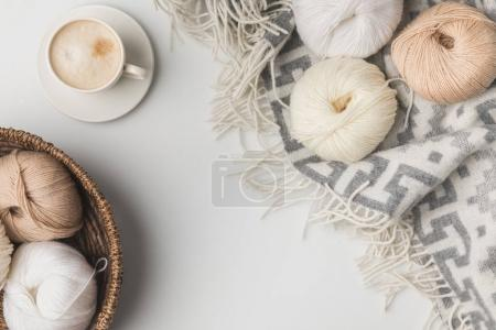 top view of yarn balls in wicker basket, cup of coffe and blanket on white background