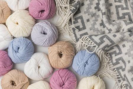 scattered colored yarn balls and blanket  on white background
