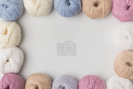 top view of colored yarn balls in a row isolated on white background