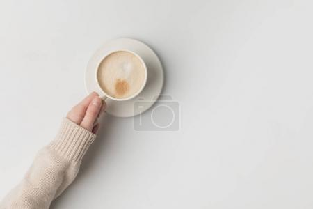 cropped view of woman holding cup of coffee in hand on white background