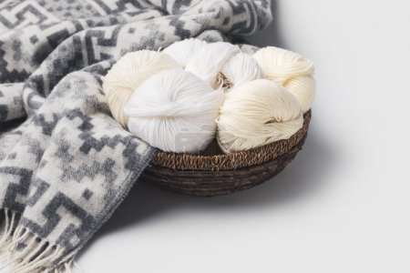 white yarn balls in wicker basket with blanket isolated on white