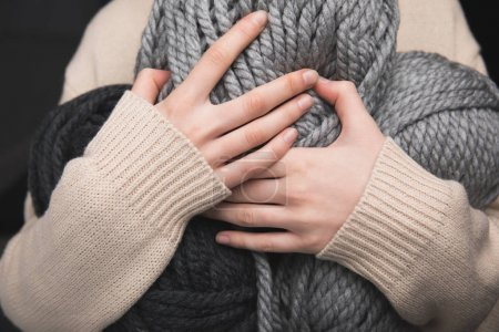 midsection of woman holding grey yarn balls in hands  on black background