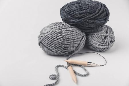 grey yarn balls and knitting needles isolated on white