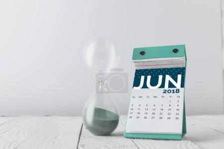 close up view of hourglass and june calendar on wooden tabletop isolated on white