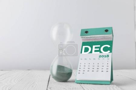 close up view of hourglass and december calendar on wooden tabletop isolated on white