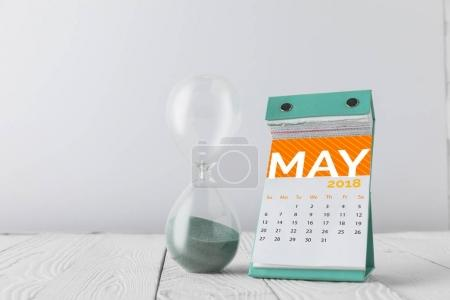 close up view of hourglass and may calendar on wooden tabletop isolated on white