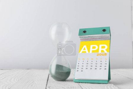 close up view of hourglass and april calendar on wooden tabletop isolated on white