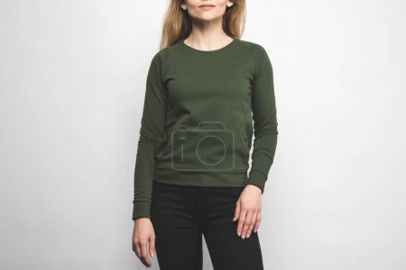 cropped shot of woman in blank green sweatshirt on white