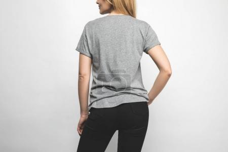 rear view of woman in blank grey t-shirt on white
