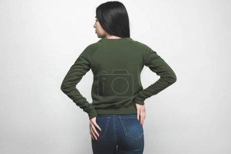 back view of young woman in blank green sweatshirt on white