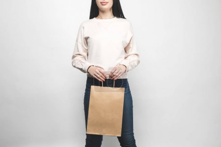 young woman in blank sweatshirt on white with shopping bag
