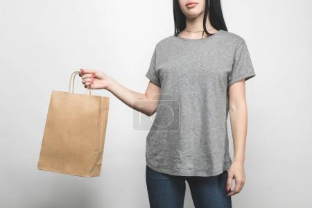 Photo pour Photo recadrée de jeune femme en t-shirt gris blanc sur blanc avec panier - image libre de droit