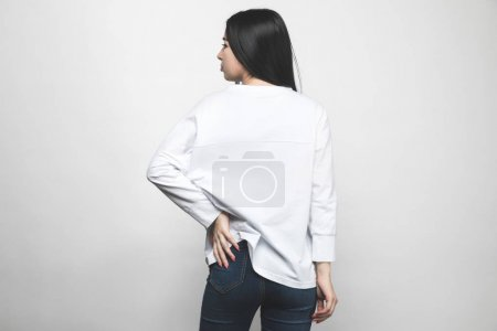 rear view of young woman in blank sweatshirt on white