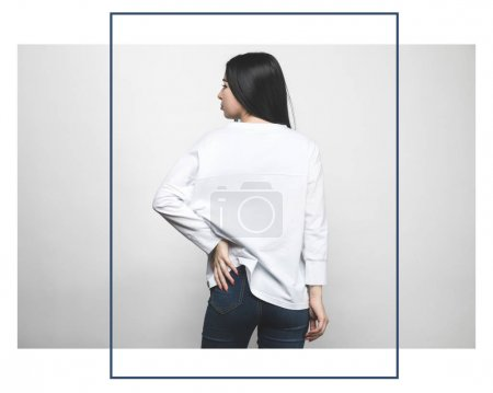 rear view of attractive woman in blank sweatshirt on white with creative frame