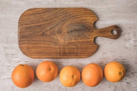 top view of row of oranges and cutting board on marble table