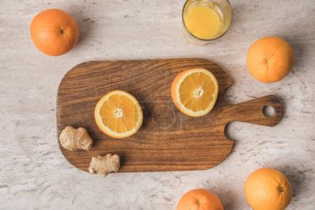 top view of cut orange and ginger on wooden board