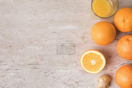 top view of oranges and orange juice on marble table