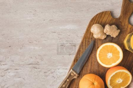 top view of oranges, knife and ginger on marble surface