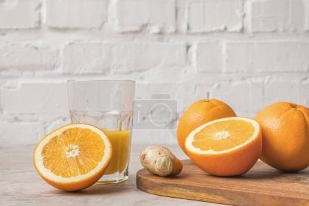 homemade orange juice and oranges with ginger on marble table