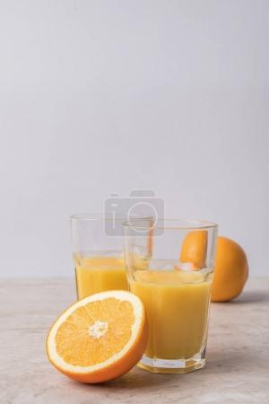 homemade orange juice and oranges on marble table