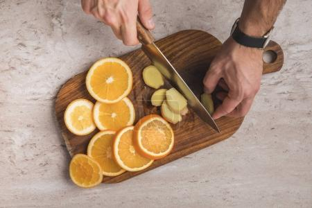 cropped image of man cutting ginger on wooden board