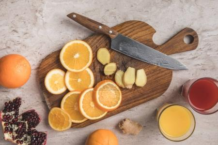 Photo for Top view of cut oranges, ginger and pomegranate with homemade juices on table - Royalty Free Image