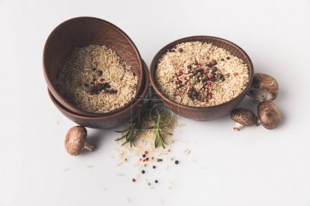 Photo pour Bols de riz cru avec des épices et des champignons sur la table blanche - image libre de droit