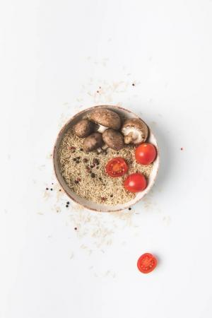 top view of raw rice in bowl with mushrooms and tomatoes on white tabletop with spilled rice and spices around