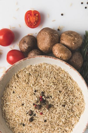 top view of raw rice and spices in bowl with mushrooms and tomatoes on white surface