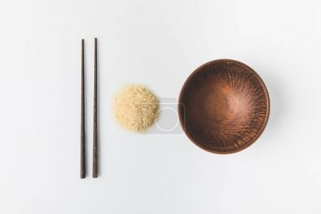 top view of raw rice heap with bowl and chopsticks isolated on white