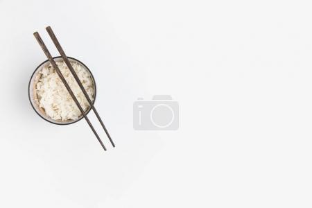 top view of bowl of rice with chopsticks isolated on white