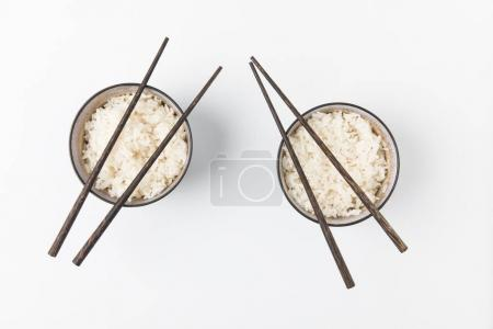 top view of bowls of tasty rice with chopsticks isolated on white