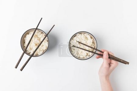 cropped shot of woman taking rice from bowl with chopsticks