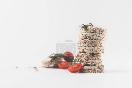 stack of rice cakes with rosemary and tomatoes on white surface