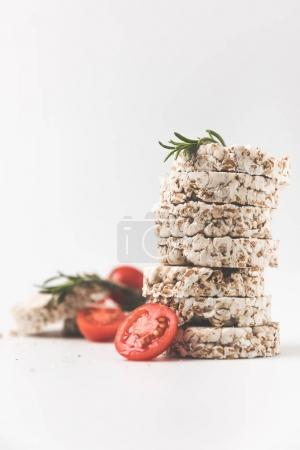 stack of rice cakes with rosemary and tomatoes on white tabletop